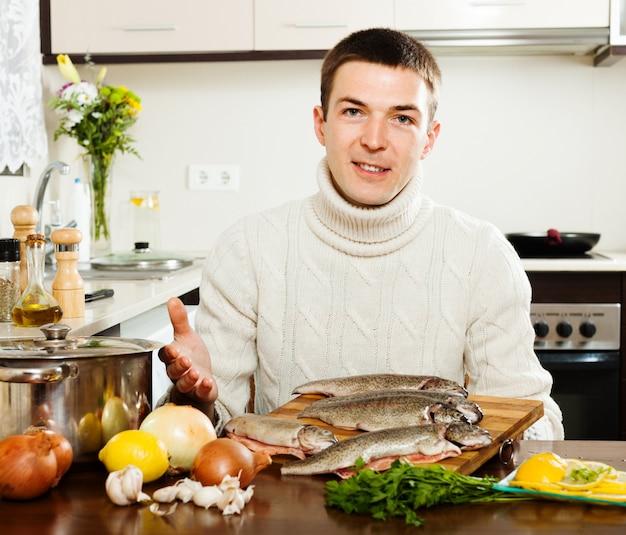 Gut aussehender mann mit forellenfischen