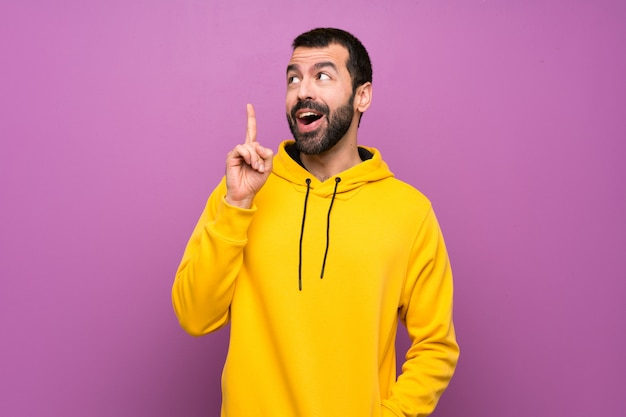 Gut aussehender mann mit gelbem sweatshirt eine idee denkend, die oben den finger zeigt