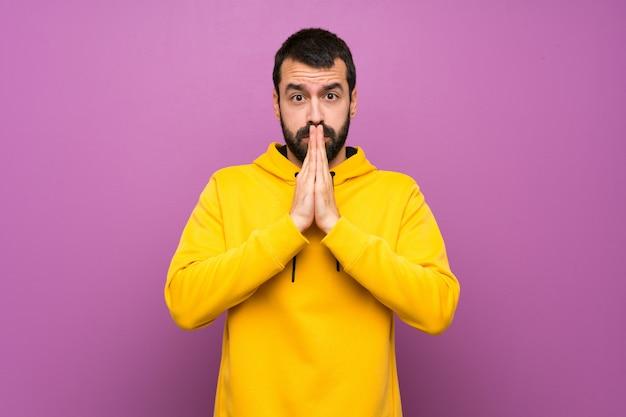 Gut aussehender mann mit gelbem sweatshirt hält palme zusammen. person bittet um etwas