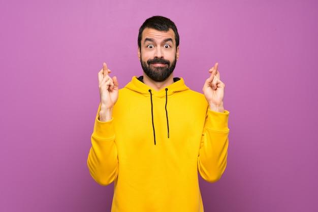 Gut aussehender mann mit gelbem sweatshirt mit den fingern, die das beste kreuzen und wünschen