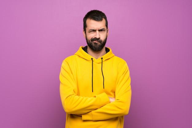 Gut aussehender mann mit gelbem sweatshirt mit traurigem und deprimiertem ausdruck