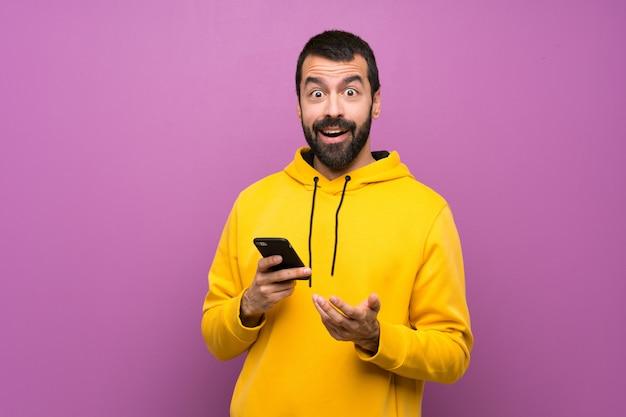Gut aussehender mann mit gelbem sweatshirt überraschte und eine mitteilung sendend