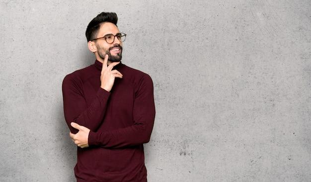 Gut aussehender mann mit gläsern eine idee beim oben schauen über strukturierter wand denkend