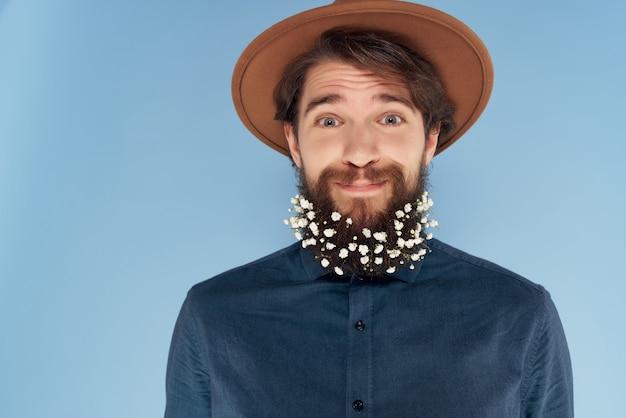 Gut aussehender mann mit hut mit blauen hemdblumen in bart-selbstbewusstseinsmode