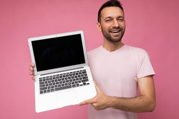 Gut aussehender mann mit laptop-computer, der die kamera im t-shirt auf isoliertem rosa hintergrund anschaut