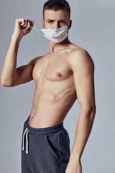 Gut aussehender mann mit medizinischem maskenschutz des nackten muskulösen oberkörpers