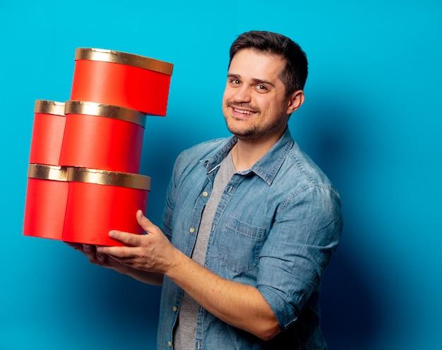 Gut aussehender mann mit roten geschenken