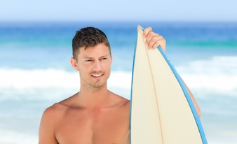 Gut aussehender Mann mit seinem Surfbrett