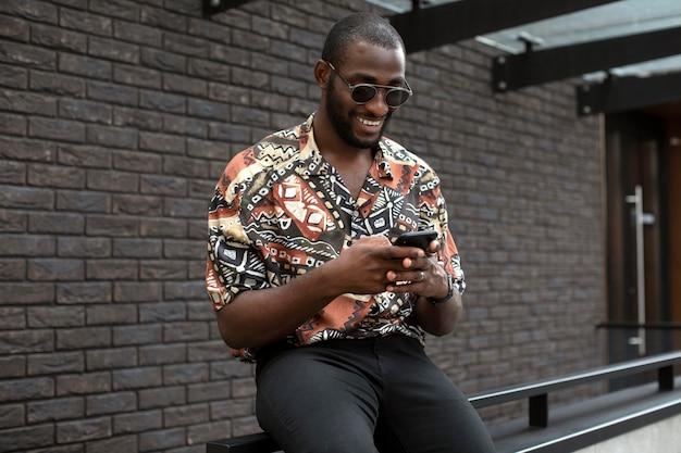Gut aussehender mann mit sonnenbrille mit modernem smartphone im freien