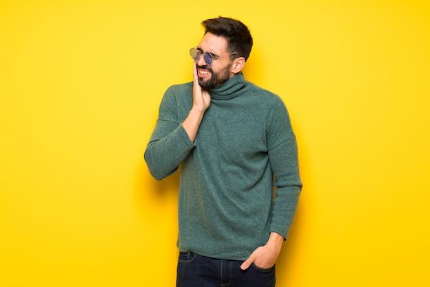 Gut aussehender mann mit sonnenbrille mit zahnschmerzen