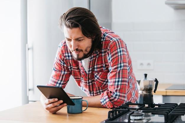Gut aussehender mann mit tasse kaffee, der handy auf küchenarbeitsplatte betrachtet