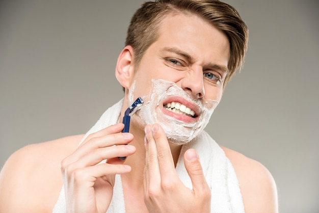 Gut aussehender mann mit tuch auf den schultern, die nach bad sich rasieren.