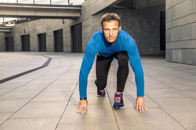 Gut aussehender mann mittleren alters in blau-schwarzer sportuniform und kopfhörer und fitness-tracker läuft in der stadt.