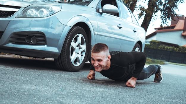 Gut aussehender mann nahe dem auto. der athlet wrang neben der maschine aus. auto vs mann
