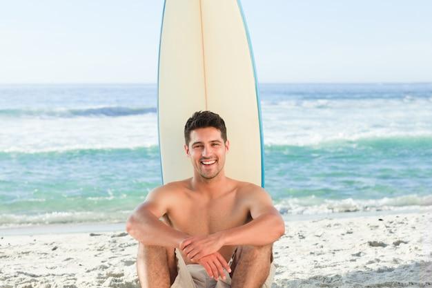 Gut aussehender mann neben dem meer mit seinem surfbrett