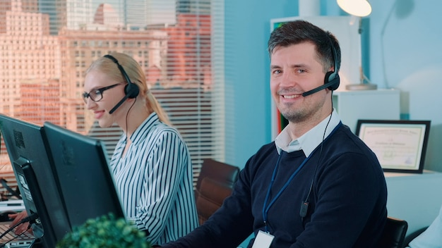 Gut aussehender mann-service-betreiber, der im callcenter mit dem kunden telefoniert. er benutzt ein headset, das menschen hilft.