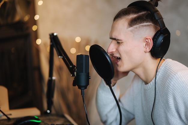 Gut aussehender mann singen zu hause von computer mann verwenden professionelle soundausrüstung wie mikrofon und