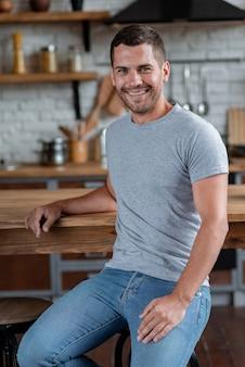 Gut aussehender mann sitzt auf dem stuhl, der auf tabelle gelehnt wird und lächelt, die kamera betrachtend.