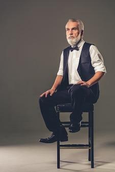Gut aussehender mann sitzt auf einem stuhl