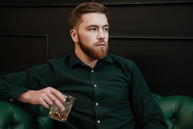 Gut aussehender mann sitzt in einem sessel und trinkt whisky