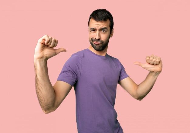 Gut aussehender mann stolz und in konzept der liebe selbst auf lokalisiertem rosa hintergrund selbstzufrieden