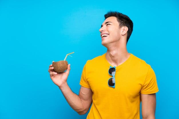 Gut aussehender mann über blau mit einer kokosnuss