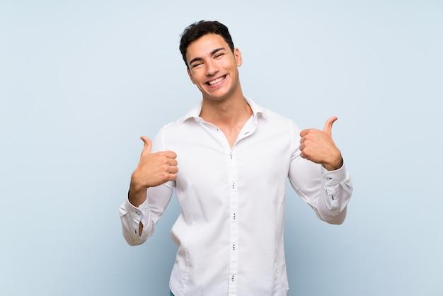 Gut aussehender mann über blauer wand mit den daumen up geste und lächeln