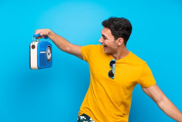 Gut aussehender mann über dem blau, das ein radio hält