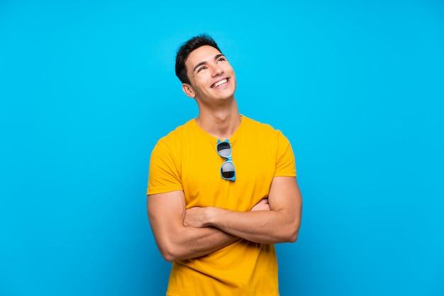 Gut aussehender mann über dem blau, das oben beim lächeln schaut