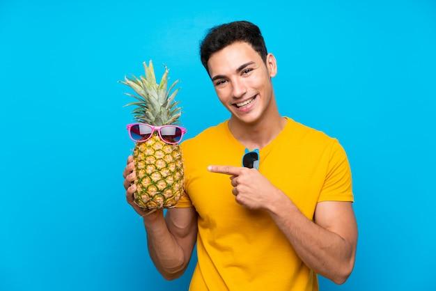 Gut aussehender mann über dem blauen hintergrund, der eine ananas mit sunglasse hält