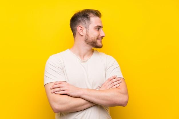 Gut aussehender mann über dem gelben hintergrund, der zur seite schaut