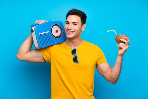 Gut aussehender mann über der blauen wand, die einen radio hält
