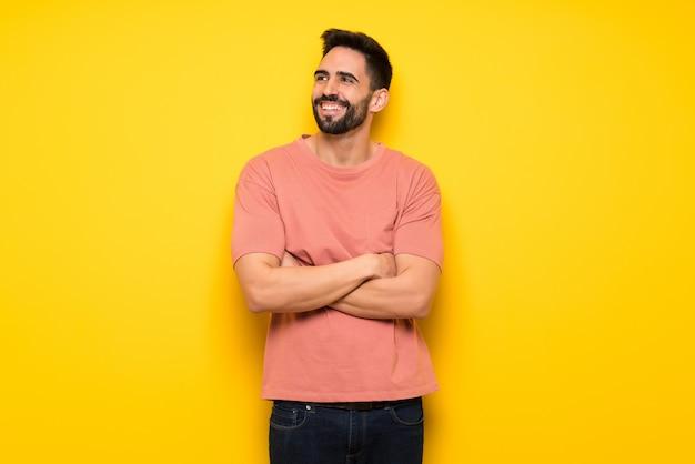 Gut aussehender mann über der gelben wand, die oben beim lächeln schaut