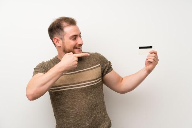 Gut aussehender mann über der lokalisierten weißen wand, die eine kreditkarte hält