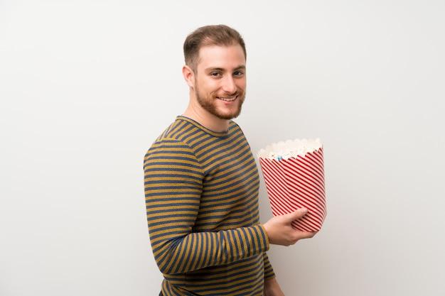 Gut aussehender mann über der lokalisierten weißen wand, die eine schüssel popcorn hält