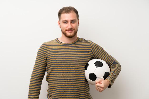 Gut aussehender mann über der lokalisierten weißen wand, die einen fußball hält