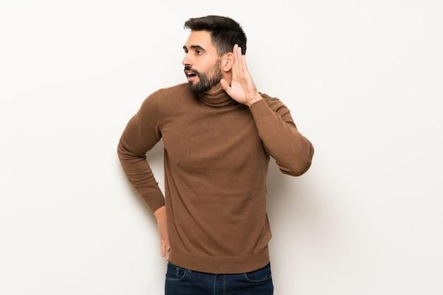 Gut aussehender mann über der weißen wand hörend auf etwas, indem er hand auf das ohr setzt