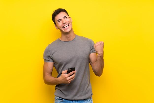 Gut aussehender mann über lokalisierter gelber wand mit telefon in siegposition