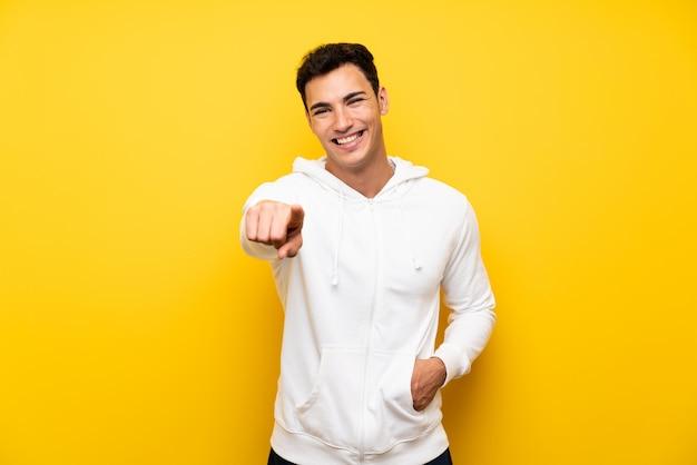 Gut aussehender mann über lokalisierter gelber wand zeigend auf die front