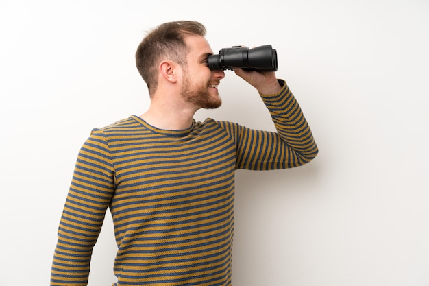 Gut aussehender mann über lokalisierter weißer wand mit schwarzen ferngläsern