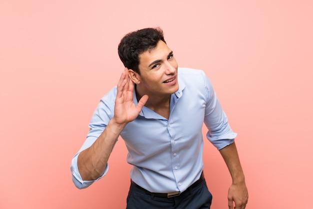 Gut aussehender mann über rosa hörend auf etwas, indem sie hand auf das ohr setzen