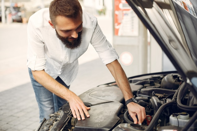 Gut aussehender mann überprüft den motor in seinem auto