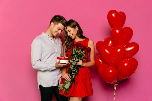 Gut aussehender mann und attraktive frau, die kasten mit geschenk, rote rosen betrachten