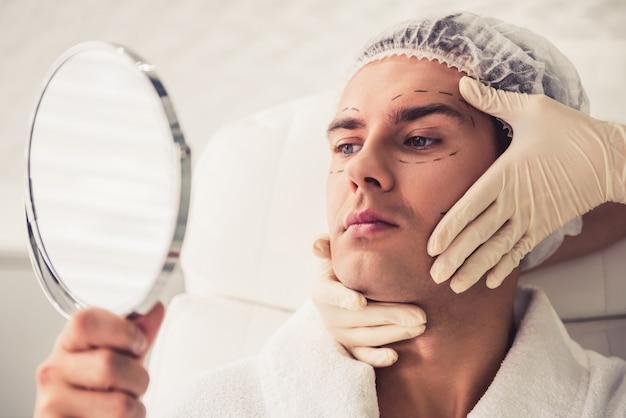 Gut aussehender mann untersucht den spiegel.