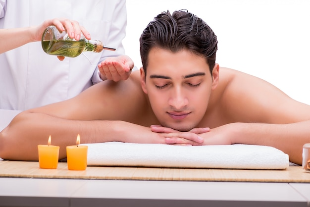 Gut aussehender mann während des badekurortes, der sitzung massiert