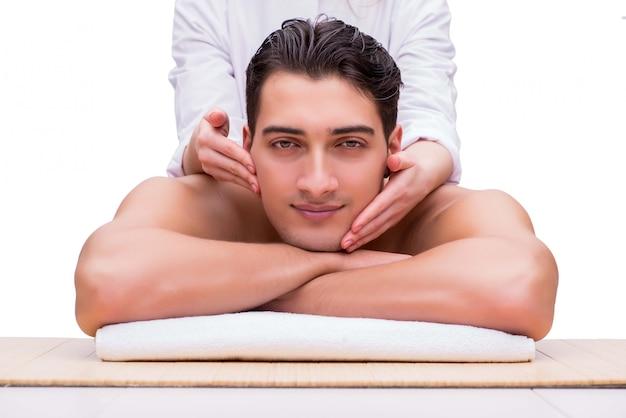 Gut aussehender mann während des badekurortes sitzung massierend