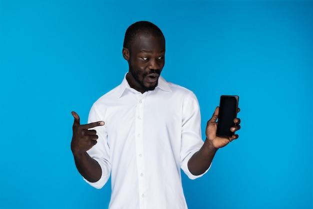 Gut aussehender mann zeigt auf das telefon