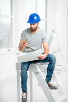 Gut aussehender mechaniker oder baumeister im helm, der mit zeichnungen und telefon bei der renovierung des wohnungsinnenraums arbeitet