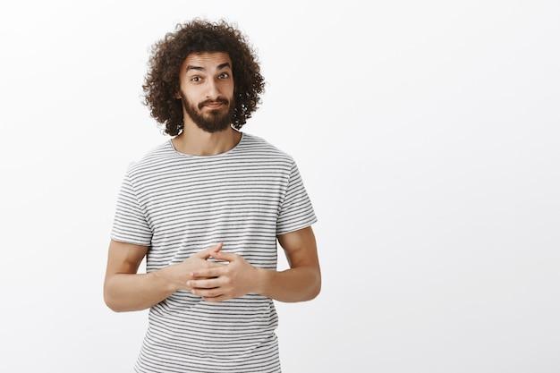 Gut aussehender spanischer bärtiger männlicher mitarbeiter mit lockiger frisur in gestreiftem t-shirt, zusammengepressten handflächen, zweifelhaft aussehend