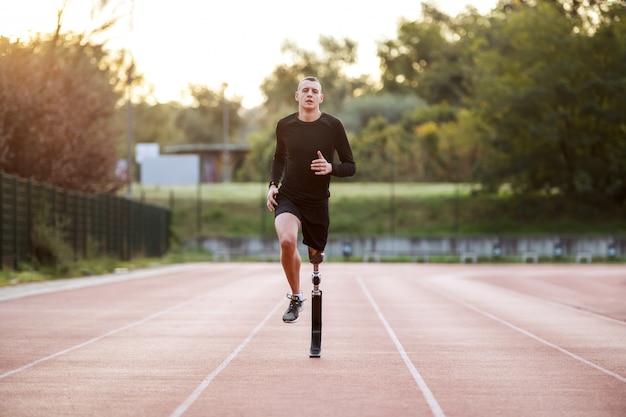 Gut aussehender sportlicher kaukasischer behinderter junger mann in sportbekleidung und mit künstlichem bein, das auf rennstrecke auf stadion läuft.